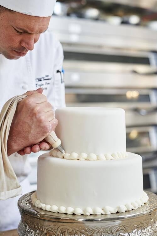 a chef adds icing to a cake