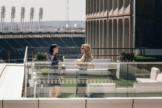 Two women speaking atop the Azure Rooftop Lounge, with Cleveland