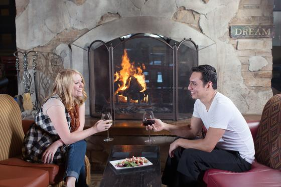Couple enjoys wine by a fireplace