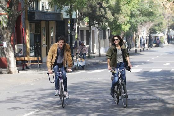 hombre y mujer andando en bicicleta por la calle en barrio lasta