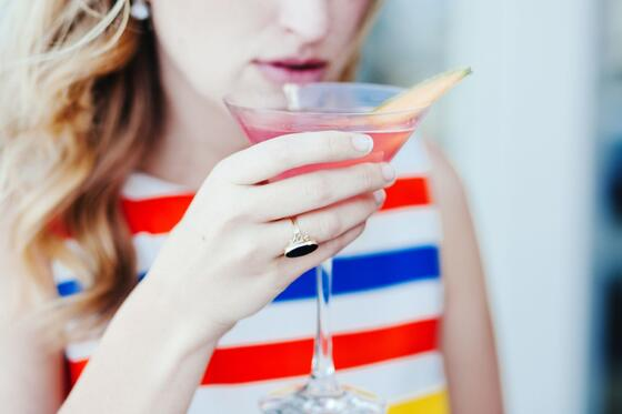 Young woman sipping a cocktail