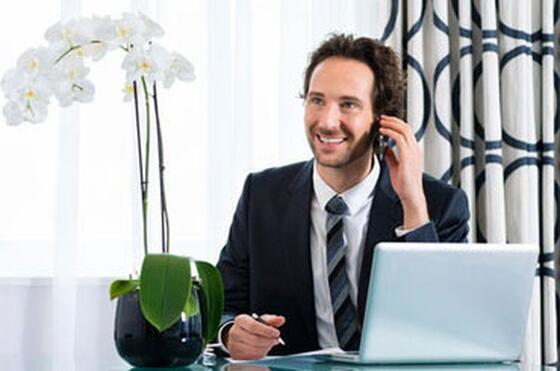 Man in a suit talking on a phone beside his laptop and an orchid