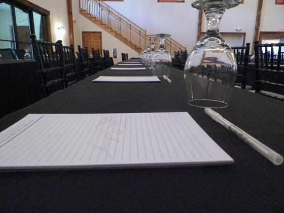 Close photo of conference table with paper and pen.