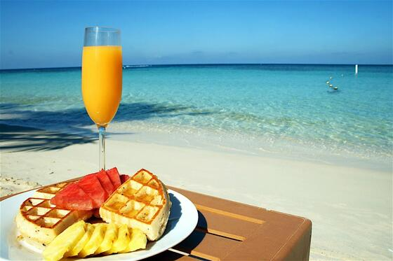 waffles with fruit and orange juice on table by the beach