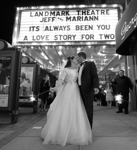 Bride and groom kissing outside of Landmark Theater