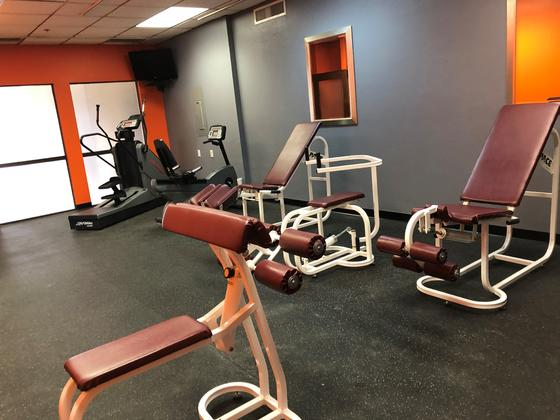 Fitness center with various workout stations.