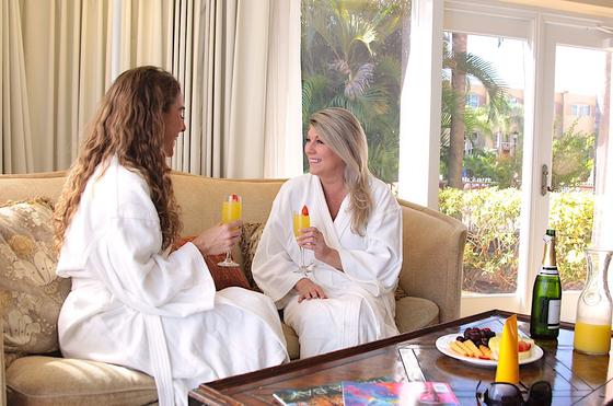 Two women in spa wobes drinking mimosas.