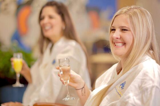 Two friends in spa robes smiling and clinking wine glasses.
