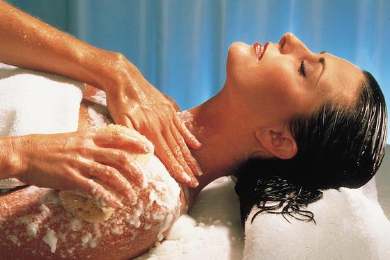 Woman receiving body polish massage.