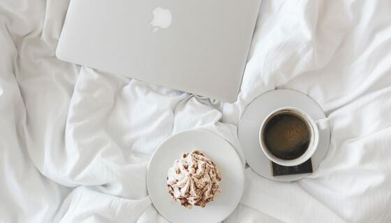 A laptop and a cup of coffee on a  bed at Vasa Hotel Surabaya