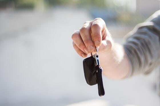 a person handing over black car keys