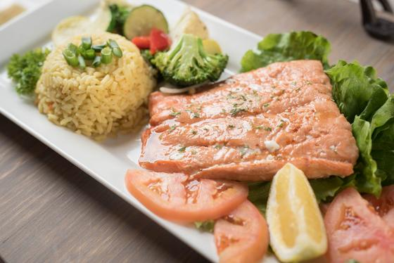 Dish of salmon, rice pilaf and fresh vegetables.