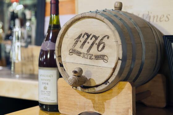 table top wine barrel next to wine bottle.