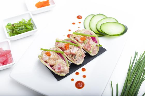 three mini tacos on a plate with sliced cucumber