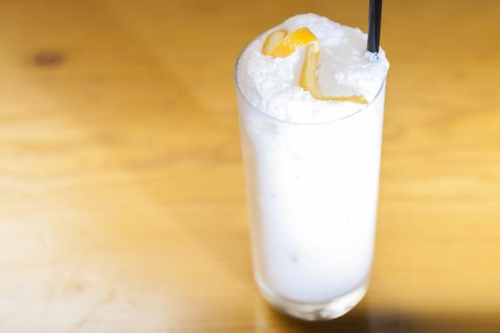 white drink in tall glass on a bar