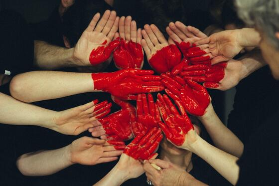 Group of hands painted red in the shape of a heart