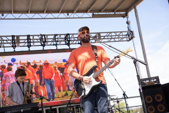 concert with guitarist in orange shirt