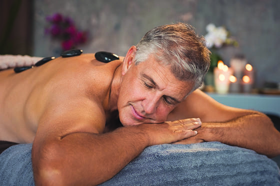 man getting massage with black stones on his back