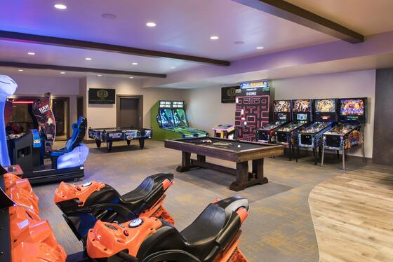 a pool table and racing games in a game room