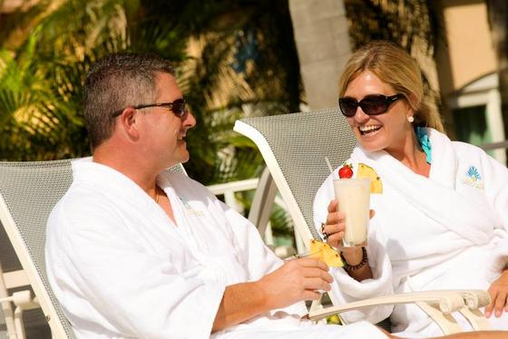 couple relaxing in robes drinking a cocktail