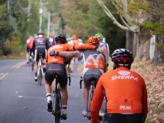 group cyclling on road in sherpa fit clothing