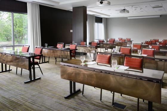 large conference room with long tables and red chairs