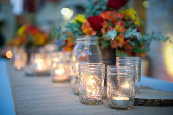 candles inside mason jars centered on table