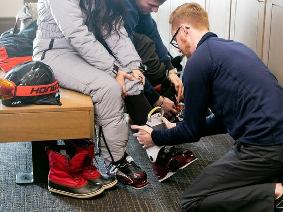 a man helps a woman put on ski boots