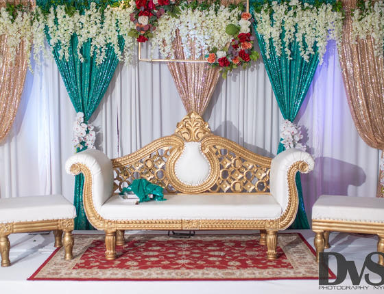 white and gold seating bench with flower wall/curtain décor