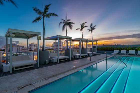 rooftop pool with cabanas at sunset