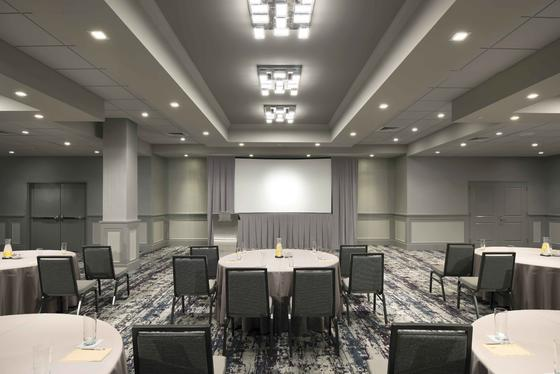 banquet room with round tables, chairs and projector screen
