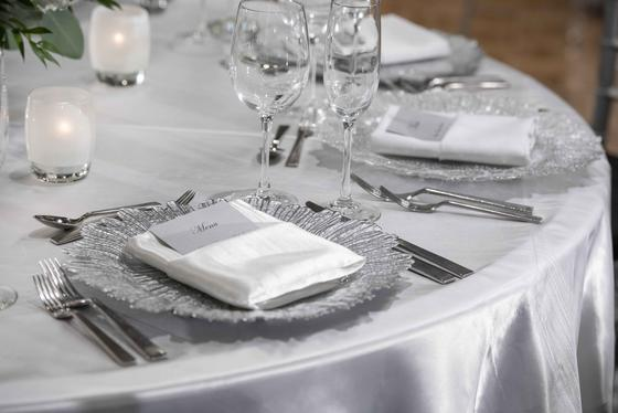 dining table with silver linen and place settings