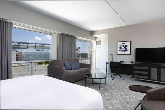 room with bed, sofa, desk and view to gillette stadium