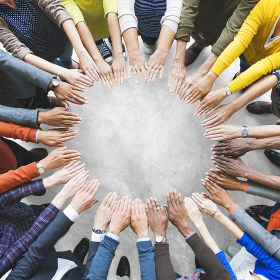 a group of people form their hands into a circle