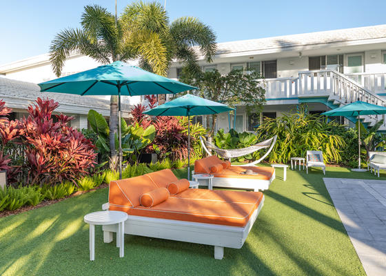 Image of day beds, open blue umbrellas, a hammock in the corner,