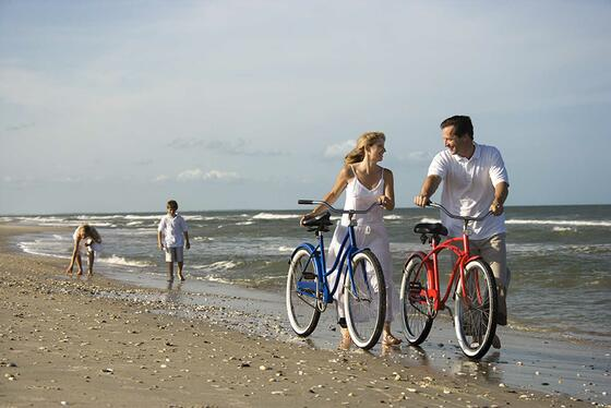 couple with bicycles and kids walking behind them