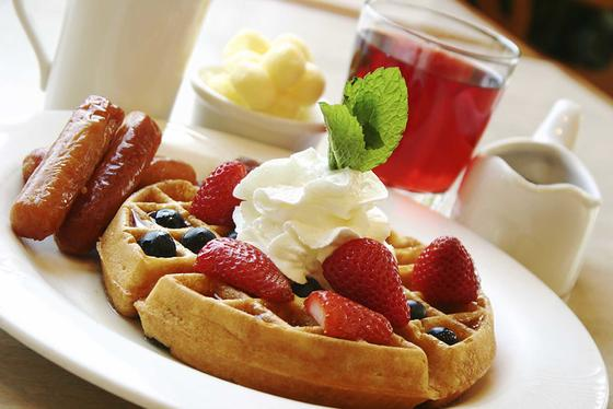 waffle with berries, whipped cream and a side of sausage