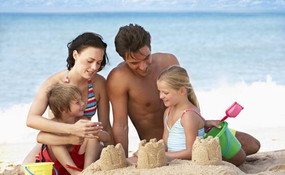 family building sand castles on beach