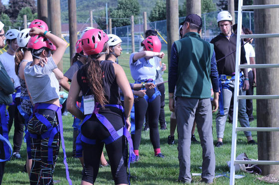 People with harnesses and helmets at ropes course