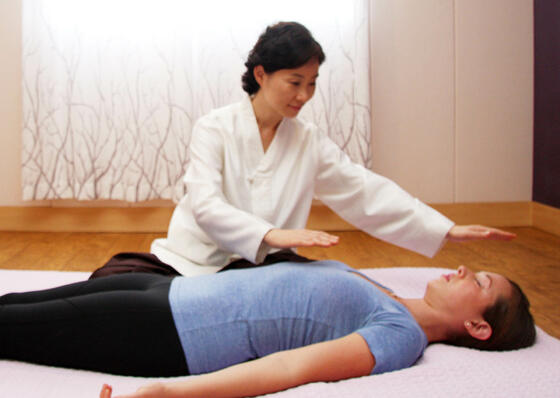 Woman doing energy healing on patient