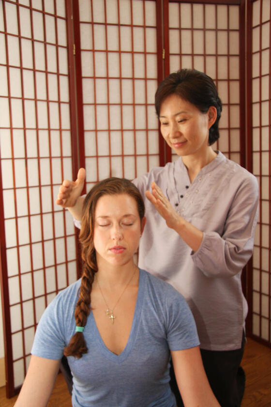 Woman doing chakra healing on client