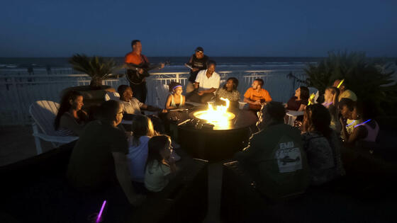 group of people sitting around firepit