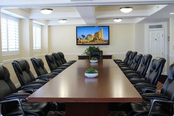 boardroom with executive chairs and television on wall