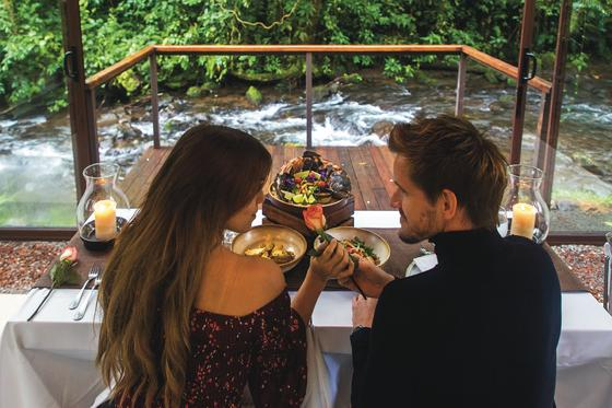couple eating at dinner table in front of river