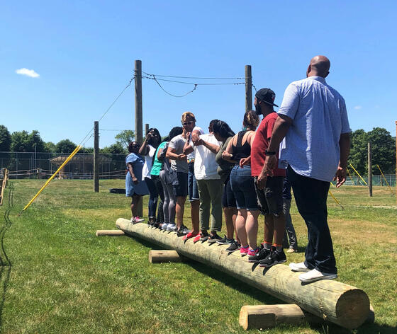 People balancing on a log