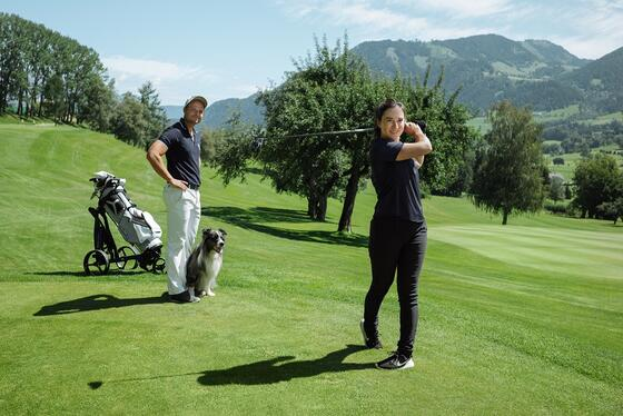 Couple with a dog on the golf course of Schloss Pichlarn