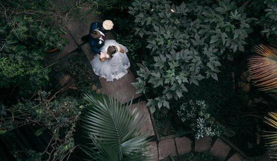 a bride and groom walking on a stone path