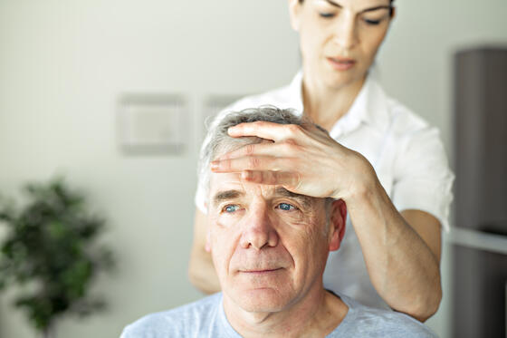 Woman feeling patient's forehead