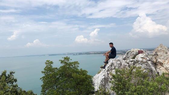 man sitting on rock at bukit batu putih of tanjung tuan port dic