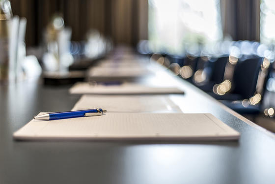 meeting room table with paper and pen